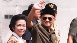 Presiden BJ Habibie didampingi istrinya Ainun Habibie melambaikan tangan kepada wartawan saat tiba di pusat perbelanjaan yang hancur akibat gelombang kekerasan di Chinatown, Jakarta, 26 Mei 1998. Habibie meninggal pada usia 83 tahun akibat gagal jantung dan menua. (AFP Photo/Kemal Jufri)
