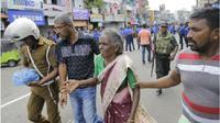 Seorang wanita tua dibantu menyelamatkan diri pasca-ledakan di St. Anthony, Sri Lanka ( Eranga Jayawardena / AP )