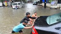 Sejumlah anak mendorong sebuah mobil yang mogok akibat melintasi banjir saat hujan deras di Mumbai, India (9/7). Mumbai dan daerah pinggiran lainnya telah mengalami hujan lebat semalaman yang mengakibatkan banjir. (AFP Photo/Indranil Mukherjee)