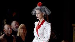 Bella Hadid berjalan di catwalk untuk show Rodarte pada New York Fashion Week: The Shows di New York City, Selasa (11/2/2020). Bella Hadid seolah-olah kembali ke era tahun 50an dalam balutan gaun polkadot merah dan putih dengan kerudung yang menutupi wajahnya. (Dimitrios Kambouris/Getty Images/AFP)