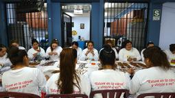 Sejumlah narapidana di penjara Wanita Virgen de Fatima duduk berkumpul membuat rosario kayu buatan tangan di Lima, Peru (12/1). (AFP Photo/Cris Bouroncle)