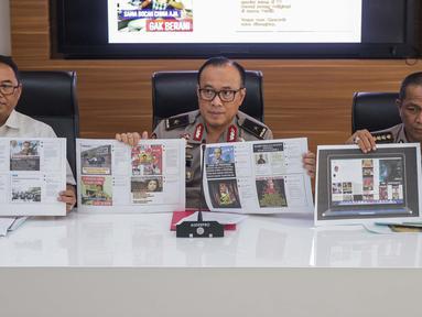 Karopenmas Divisi Humas Polri Brigjen Pol Dedi Prasetyo (tengah) dan Kasubdit I Dittipidsiber Bareskrim Polri Kombes Pol Dani Kustoni (kiri) menunjukkan barang bukti kasus pemberitaan hoax di Divhumas Mabes Polri, Jakarta, Senin (1/7/2019). (Liputan6.com/Faizal Fanani)