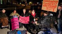 Sejumlah penyandang cacat melakukan protes dengan cara yang tidak biasa. Mereka saling merantai kursi-kursi roda.