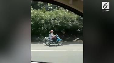 Seorang pengendara mobil yang tengah melintasi Tol Tangerang merekam aksi emak-emak yang nekat masuk ke jalur tol sambil bonceng anak.