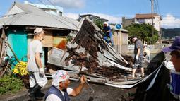 Topan Haishen di Jepang: Warga memperbaiki atap yang rusak akibat angin kencang menyusul topan Haishen di Amami, prefektur Kagoshima, barat daya Jepang, Senin (7/9/2020). Topan kuat kedua yang melanda wilayah itu dalam sepekan ini menyebabkan korban terluka dan bangunan rusak. (Kyodo News via AP)