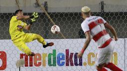 Kiper PSS Sleman, Ega Rizky menghalau tendangan dari bek Madura United, Jaimerson Xavier dalam laga Grup C Piala Menpora 2021 di Stadion Si Jalak Harupat, Bandung, Selasa (23/3/2021). PSS Sleman kalah 1-2 dari Madura United. (Bola.com/M Iqbal Ichsan)