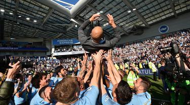 Pelatih Manchester City, Pep Guadiola, diangkat pemainnya saat merayakan gelar juara Liga Inggris di Stadion American Express Community, Brighton, Minggu (12/5). City juara setelah unggul satu poin dari Liverpool. (AFP/Glyn Kirk)