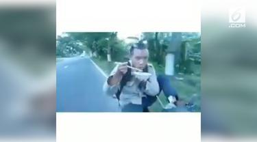 Seorang pria nekat kendarai motor sambil makan mie ayam. Ia melakukan aksinya hanya dengan satu kaki.