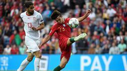 Gelandang Portugal Joao Felix (kanan) berusaha menendang bola dari kawalan bek Swiss, Ricardo Rodriguez saat pertandingan semifinal Liga Bangsa-Bangsa UEFA di stadion Dragao di Porto pada 5 Juni 2019. (AFP Photo/Miguel Riopa)