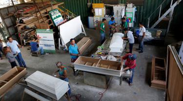 Para mantan pengguna narkoba membuat peti mati di kota Olongapo, Filipina utara, (5/10). Kegiatan ini merupakan bagian dari program rehabilitasi pemerintah setempat bagi mereka yang terjerumus dalam penyalahgunaan narkoba. (REUTERS/Erik De Castro)
