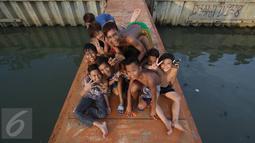 Keseruan anak-anak berfoto saat bermain dan mandi di anak Kali Ciliwung, Jakarta, Rabu (13/7). Bersihnya kali yang berada di Ibu Kota itu dimanfaatkan anak-anak sekitar untuk berenang sambil mengisi waktu libur sekolah. (Liputan6.com/Immanuel Antonius)