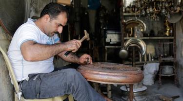 Ahmad Zuhdi Ghazoul menyelesaikan pekerjaannya di pasar tembaga yang baru direnovasi di Aleppo, Suriah, Minggu (28/7/2019 ). Kegiatan ekonomi perlahan mulai tumbuh tiga tahun setelah pertempuran besar terjadi di Aleppo. (AP Photo/Hassan Ammar)