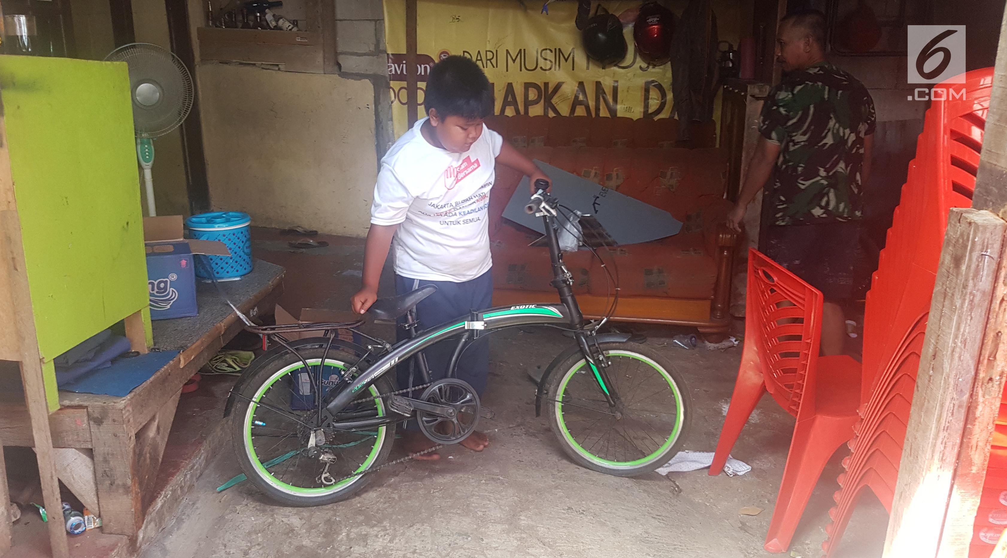 Fadli yang Berjualan Donat Kentang Setelah Pulang Sekolah Ini Memperlihatkan Sepeda yang Diberikan Deddy Corbuzier (Liputan6.com/Aditya Eka Prawira)