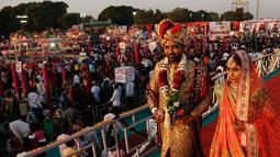 Sepasang pengantin berjalan bersama saat nikah massal di Surat, India, Minggu (23/12). Sebanyak 261 pasangan mengikuti acara nikah massal kali ini. (AP/Ajit Solanki)