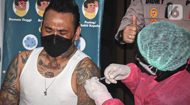 Musikus I Gede Ari Astina alias Jerinx menerima suntikan vaksin COVID-19 di Biddokkes Polda Metro Jakarta, Sabtu (15/8/2021). Jerinx mengaku telah berkonsultasi dan berdiskusi panjang dengan dokter ahli Virology sampai akhirnya memutuskan untuk menggunakan vaksin Sinovac (Liputan6.com/Faizal Fanani)