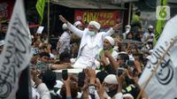Rizieq Shihab menyapa massa pendukungnya saat tiba di kediamannya di Jalan Petamburan, Jakarta, Selasa (10/11/2020). Rizieq Shihab tiba di kediamannya usai pulang dari Arab Saudi. (merdeka.com/Imam Buhori)