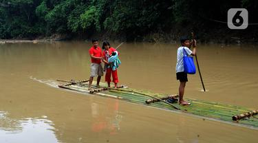 Warga menyeberangi Sungai Cikaniki dengan rakit di Rumpin, Bogor, Jawa Barat, Rabu (15/1/2020). Akibat banjir bandang merobohkan jembatan yang menghubungkan Desa Tonjong Rumpin dan Desa Kantalarang Leuwiliang, warga terpaksa memanfaatkan perahu rakit untuk melintas. (merdeka.com/Arie Basuki)