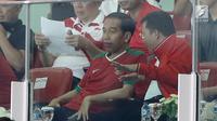 Presiden Joko Widodo berbincang dengan Menpora ketika menonton langsung final Piala Presiden 2018 antara Persija vs Bali United di Stadion Utama Gelora Bung Karno, Senayan, Jakarta, Sabtu (17/2) (Liputan6.com/Arya Manggala)