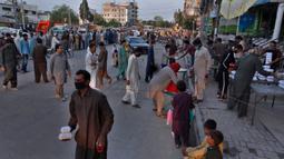 Orang-orang menerima kotak makanan dan minuman manis tradisional untuk berbuka puasa di Rawalpindi, Pakistan, Minggu, (3/5/2020). Umat Muslim di seluruh dunia sedang melaksanakan Ramadan untuk menahan diri dari makan, minum sejak subuh sampai senja. (AP/Anjum Naveed)