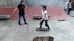 Instruktur melatih seorang anak menggunakan skateboard dengan memakai masker dan face shield di Crooz Shophouse di kawasan Duren Tiga, Jakarta Selatan, Minggu (2/8/2020). Mereka kembali melakukan latihan seminggu dua kali dengan menerapkan protokol kesehatan. (merdeka.com/Arie Basuki)