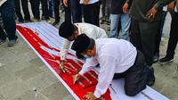 Tokoh Nahdatul Ulama Riau, Rusli Ahmad (kiri) menandatangani penolakan Rizieq Shihab dalam aksi damai di Pekanbaru. (Liputan6.com/M Syukur)
