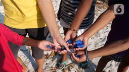 Aktivis AS, Carrie (kedua kiri) dan anak-anak menunjukkan sampah plastik di Desa Sawandarek, Raja Ampat, Papua Barat (22/11/2019). Carrie mengajak anak-anak untuk membersihkan sampah setiap Jumat dengan berkunjung ke sejumlah desa atau pulau yang ada di Raja Ampat. (Liputan6.com/Herman Zakharia)