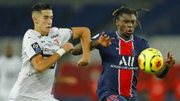 Penyerang Paris Saint-Germain (PSG), Moise Kean, berebut bola dengan pemain Renners, Nayef Aguerd, pada laga Liga Prancis di Stadion Parc des Princes, Sabtu (7/11/2020). PSG menang dengan skor 3-0. (AP/Christophe Ena)