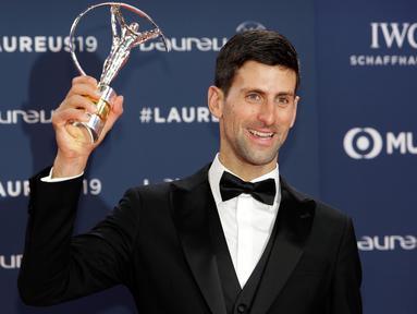 Petenis Serbia, Novak Djokovic berpose dengan trofi World Sportsman of the Year dalam ajang Laureus World Sports Awards 2019 di Monako, Senin (18/2). Djokovic mengalahkan Kylian Mbappe, LeBron James, Luka Modric dan Lewis Hamilton. (AP/Claude Paris)