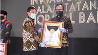 Menkes Terawan menyerahkan penghargaan inovasi pada era new normal kepada Wali Kota Bogor Bima Arya.