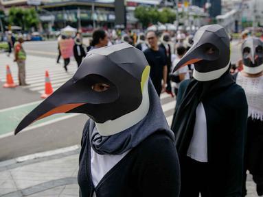 Sejumlah aktivis Greenpeace mengenakan topeng penguin saat menggelar aksi dalam car free day di kawasan Thamrin, Jakarta, Minggu (9/2/2020). Mereka mengajak pemerintah untuk berpartisipasi dalam mewujudkan Perjanjian Laut Internasional (Global Ocean Treaty). (Liputan6.com/Faizal Fanani)