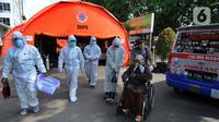 Petugas mengevakuasi pasien COVID-19 untuk menjalani perawatan di dalam tenda darurat di RSUD Kota Bekasi, Jumat (25/06/2021). Puluhan pasien covid-19 saat ini dirawat dalam tenda darurat karena keterisian tempat tidur yang penuh akibat lonjakan kasus. (merdeka.com/Arie Basuki)