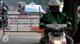 Sebuah spanduk berisi pelarangan masuk kepada Go-Jek dan Grab Bike terpasang di kawasan Kalibata City, Jakarta, Rabu (8/7/2015). Sejumlah pengojek regular menolak keberadaan ojek online. (Liputan6.com/JohanTallo)