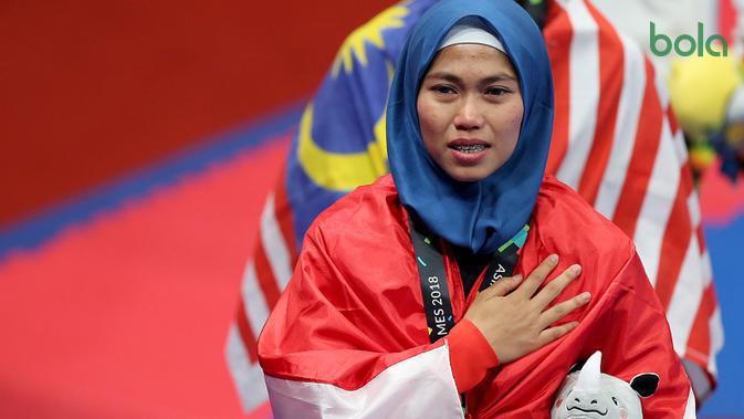 Atlet taekwondo Indonesia, Defia Rosmaniar, tampak haru saat penerimaan medali pada Asian Games 2018 di JCC, Jakarta, Minggu (19/8/2018). Defia menang dengan skor 8.690-8.470 atas wakil Iran Salahshouri Marjan. (Bola.com/Peksi Cahyo)