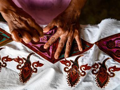 Seorang pekerja membuat desain batik di sebuah bengkel di Banda Aceh, Aceh, Rabu (13/10/2021). Batik Aceh memiliki ciri khas tersendiri, yaitu menggunakan perpaduan unsur alam dan budaya dari masyarakat Aceh sendiri. (Chaideer MAHYUDDIN/AFP)