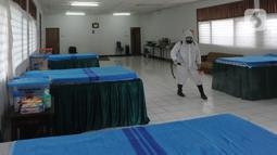 Petugas gugus tugas Covid-19 RW 03 menyemprotkan desinfektan pada tempat tidur untuk isolasi mandiri di Gedung Sasana Krida Karang Taruna, Kelurahan Pondok Labu, Jakarta, Selasa (19/1/2020). Gedung itu disulap oleh warga setempat untuk dijadikan tempat isolasi mandiri. (merdeka.com/Arie Basuki)