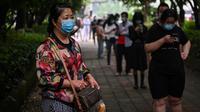 Warga mengenakan masker menunggu dalam barisan untuk tes virus corona di lingkungan di Wuhan, provinsi Hubei, Jumat (15/5/2020). Tes massal yang ditargetkan dalam 10 hari ini akibat adanya pasien Virus Corona baru di Wuhan, setelah sebulan lebih tidak ada laporan kasus baru. (Hector RETAMAL/AFP)
