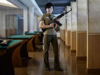 Dalam foto yang diambil pada 29 Juli 2018, seorang instruktur menembak bernama Kim Ju Yang (20) memegang senapan serbu buatan Korea saat berpose untuk sesi foto di Meari Shooting Range, Pyongyang di Korea Utara. (AFP PHOTO / Ed JONES)