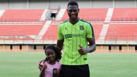 Striker Persebaya Surabaya, Amido Balde, ditemani sang putri, Aixa Balde, saat berlatih di Stadion Gelora Bung Tomo, Surabaya, Jumat (10/5/2019). (Bola.com/Aditya Wany)