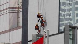 Pekerja membersihkan salah satu gedung bertingkat di Bundaran Hotel Indonesia, Jakarta, Rabu (14/3). BPJS Ketenagakerjaan mengeluarkan nilai klaim Rp 971 miliar sepanjang 2017.  (Liputan6.com/Angga Yuniar)