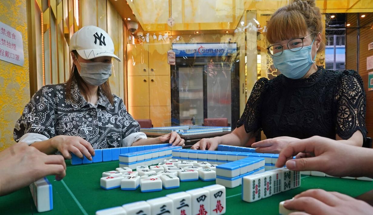 Staf yang mengenakan masker memperagakan langkah-langkah keamanan kepada media di ruang tamu mahjong di Hong Kong, Rabu (28/4/2021). Pejabat kesehatan Hong Kong mengumumkan bahwa mereka akan melonggarkan langkah-langkah terkait COVID-19 mulai 29 April 2021. (AP Photo/Kin Cheung)