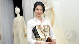 Laura Basuki mengenakan shirt dress dominan putih saat menghadiri pameran busana karya Didi Budiarjo di Museum Tekstil, Kamis (15/1/2015). (Liputan6.com/Panji Diksana)