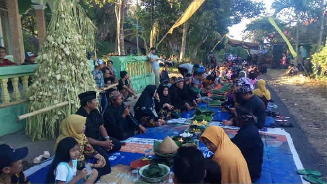 Puluhan warga berebut ribuan ketupat yang disusun menyerupai sebuah gunung di Dusun Kampung Baru, Desa/Kecamatan Glagah, Selasa (11/6/2019). Rangkaian ketupat yang menyerupai gunung ini disebut Kupat Gunggung. (/ Dian Kurniawan)