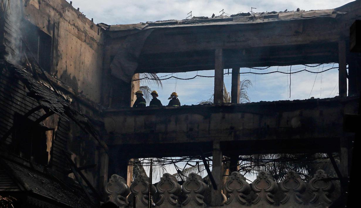 Petugas pemadam kebakaran memeriksa Hotel Istana Kandawgyi usai kebakaran di Yangon, Myanmar (19/10). Api telah melahap hotel bintang lima yang sering dikunjungi wisatawan asing di kota Yangon, Myanmar. (AP Photo/Thein Zaw)