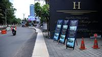 Papan nama promosi terlihat di luar hotel di jalan utama yang sepi saat Pemberlakuan Pembatasan Kegiatan Masyarakat (PPKM) Level 3 di Kuta, Badung, Bali, Jumat (23/7/2021). Selama PPKM Level 3 di Bali, tempat usaha boleh buka hingga pukul 21.00 Wita. (SONNY TUMBELAKA/AFP)