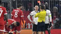 Wasit memberikan kartu merah kepada bek Besiktas, Domagoj Vida, saat melawan Bayern Munchen pada laga Liga Champions di Stadion Allianz Arena, Munchen, Selasa (20/2/2018). Munchen menang 5-0 atas Besiktas. (AFP/Thomas Kienzle)