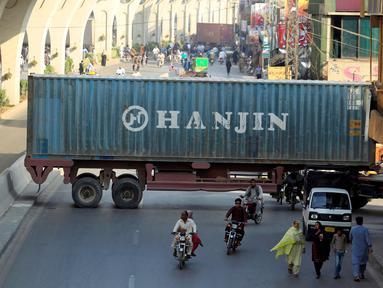 Sejumlah pengendara motor melewati kolong sebuah truk kontainer di Rawalpindi, Pakistan (28/10). Kejadian ini akibat sejumlah truk kontainer memblokir jalan raya selama demo yang digelar Awami Muslim League (AML). (Reuters/Faisal Mahmood)