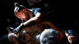 Seorang seniman  mentato badan pengunjung wanita dalam acara edisi keempat Montreux Tattoo Convention di Montreux, Swiss  (22/9). Montreux Tattoo Convention berlangsung selama tiga hari. (Valentin Flauraud/Keystone via AP)