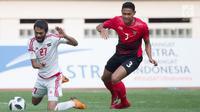 Pemain Uni Emirat Arab (UEA), Zayed Alameri (kiri) terjatuh saat berebut bola dengan bek Indonesia Andy Setyo pada laga Asian Games 2018 di Stadion Wibawa Mukti, Jawa Barat, Jumat (24/8). (Bola.com/Vitalis Yogi Trisna)