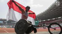 Pebalap kursi roda Indonesia, Jaenal Aripin, berselebrasi usai meraih medali perak Asian Para Games pada cabang atletik nomor balap kursi roda 200 meter T 54 di SUGBK, Jumat (12/10). Jaenal mencatatkan waktu 26,21 detik. (Bola.com/Vitalis Yogi Trisna)