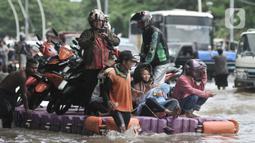 Pengendara sepeda motor menggunakan jasa rakit saat banjir melanda Cempaka Putih, Jakarta, Minggu (23/2/2020). Pengendara memanfaatkan jasa angkutan rakit yang ditawarkan warga agar dapat melewati banjir. (merdeka.com/Iqbal S. Nugroho)